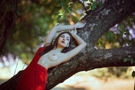 Sensual sexy fashion model with naked breast resting in fantastical forest. Photo of seductive nude woman in luxury long red dress laying on tree. Multi-racial Asian Caucasian girl. Fashionable toning. Creative computer colors. 免版税图像