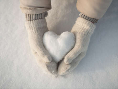 Snow heart in hands. Human hands in warm beige gloves with snowy heart against snow background. I love winter or St.Valentines Day romantic creative concept.
