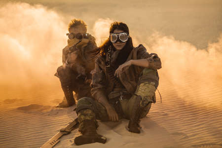 Post apocalyptic woman and boy with weapons outdoors. Desert in smoke and dead wasteland on the background. Aggressive girl warrior in shabby clothes holding sword and young boy with gun and chain sitting in a confident pose looking at camera. Nuclear post-apocalypse time. Life after doomsday concept.