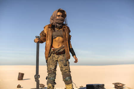 Post-apocalyptic woman with weapon outdoors. Young slim girl warrior in shabby clothes holding sword standing in a confident pose looking away. Nuclear post-apocalypse time. Life after doomsday concept. Desert and dead wasteland on the background. Reklamní fotografie