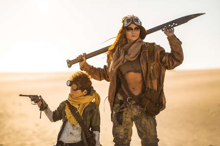 Post-apocalyptic woman and boy with weapons outdoors. Desert and dead wasteland on the background. Aggressive girl warrior in shabby clothes holding the sword and young boy with a gun standing in a confident pose looking away. Nuclear post-apocalypse time. Life after doomsday concept.