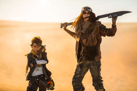 Post apocalyptic woman and boy with weapons outdoors. Desert in smoke and dead wasteland on the background. Young slim girl warrior in shabby clothes holding sword and young boy with gun standing in a confident pose looking at camera. Nuclear post-apocalypse time. Life after doomsday concept.