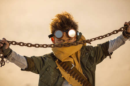 Post-apocalyptic cyberpunk boy outdoors. Nuclear post-apocalypse time. Life after doomsday concept. A young man warrior with chain in shabby clothes threaten, standing in an aggressive pose, desert and dead wasteland on the background. Closeup portrait.