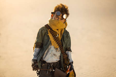 Post-apocalyptic cyberpunk boy outdoors. Nuclear post-apocalypse time. Life after doomsday concept. A young man warrior with chain, gas mask, in shabby clothes standing in an aggressive pose, desert and dead wasteland on the background.
