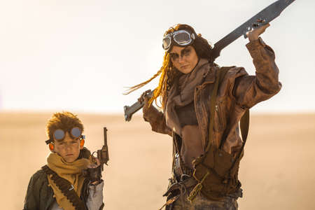 Post-apocalyptic woman and boy with weapons outdoors. Desert and dead wasteland on the background. Aggressive girl warrior in shabby clothes holding the sword and young boy with a gun standing in a confident pose looking at the camera. Nuclear post-apocalypse time. Life after doomsday concept. Reklamní fotografie