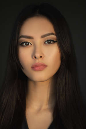 Asian woman beauty face closeup portrait. Beautiful young girl in black dress posing indoors looking at the camera. Close-up fashion portrait of Asian female model with perfect makeup isolated on a dark studio background. Banco de Imagens