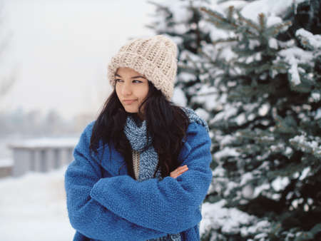 Unhappy winter woman in beautiful warm coat hat and scarf outdoors. Funny portrait image of Asian Caucasian female model standing outdoors in a winter city park. The girl looking away