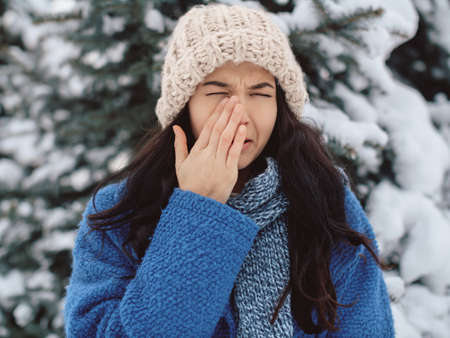 Winter woman crying outdoors. Unhappy winter woman in beautiful warm coat hat and scarf outdoors. Funny portrait image of Asian Caucasian female model standing outdoors in a winter city park.