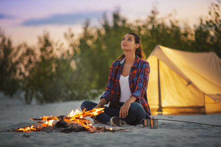 Young beautiful woman camping sitting near a campfire against orange tent on a beach in the evening. Attractive mixed race Asian Caucasian tourist girl resting looking to the sky near the fire wearing casual shirt and jeans outdoors on nature. Tourism and travel concept photo