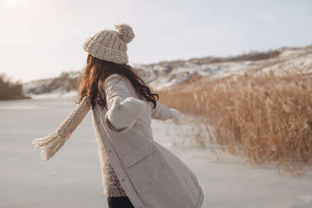 Freedom and happy wintertime concept. Happy girl spinning and raising her hands up on the frozen river on nature. Woman outdoor winter activities, female having fun at Christmastime. Banque d'images