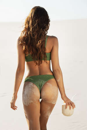 Rear view of female tanned body, sexy woman. Sporty back of a beautiful woman in green bikini with a pineapple in her hands on the beach tropical background with copyspace.