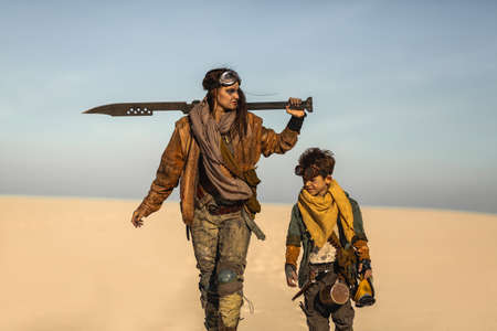 Post apocalyptic woman and boy heroically walking with weapons outdoors.