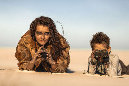 Post apocalyptic woman and boy with binoculars outdoors. Desert and dead wasteland on the background.