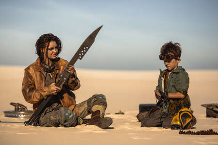 Post apocalyptic woman and boy resting in the camp outdoors. Dead wasteland on the background. Reklamní fotografie