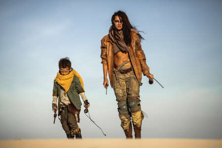 Post apocalyptic woman and boy heroically walking with weapons outdoors. Gray sky and dead wasteland on the background.