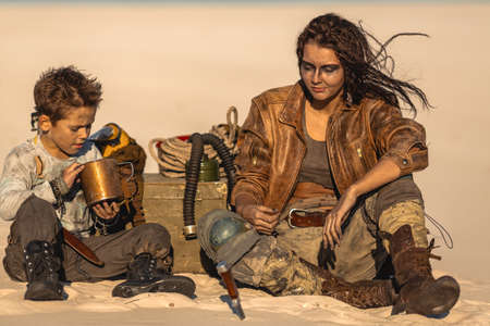 Post apocalyptic woman and boy sitting in the camp outdoors. Dead wasteland and some junk on the background.