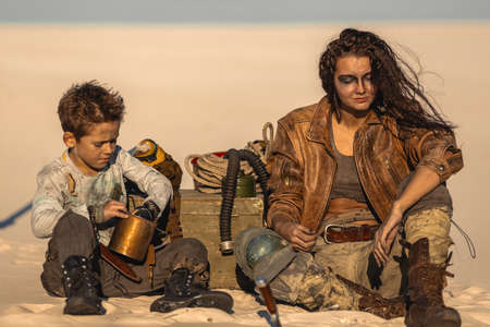 Post apocalyptic woman and boy sitting in the camp outdoors. Dead wasteland and some junk on the background. Foto de archivo - 135466971