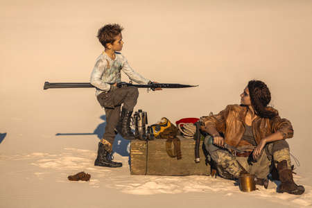 Post apocalyptic woman and boy resting in the camp outdoors. Dead wasteland on the background.