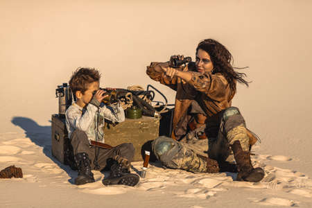 Post apocalyptic hero woman and boy with binoculars outdoors. Desert and dead wasteland on the background. Foto de archivo - 135466969