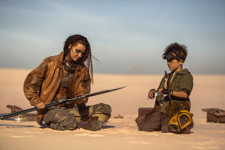 Post apocalyptic woman and boy resting in the camp outdoors. Dead wasteland on the background. Foto de archivo - 135466972