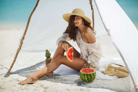 Woman holding watermelon and resting on the beach near the water. Tropical fruit diet concept. Summer holiday idyllic. Foto de archivo - 135466973