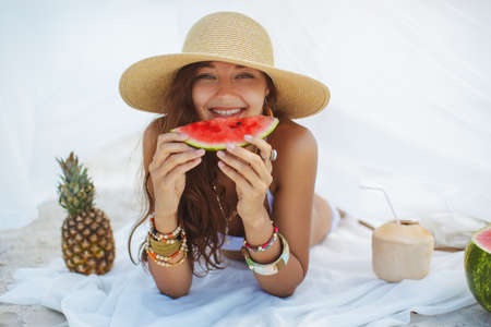 Beautiful woman holding watermelon and resting on the beach near the water. Tropical fruits diet concept. Summer holiday idyllic. Foto de archivo - 135466974