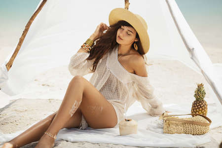 Travel vacation, summer pleasure concept. Attractive brunette woman sitting on a deserted beach under the handmade tent.