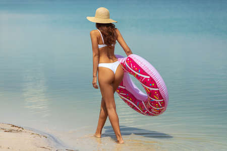 Vacation in paradise resort creative concept photo. Young beautiful woman in bikini and hat relaxing on the beach near the sea with a rubber ring. Happy girl walking with an inflatable colorful donut by the shore in summer sunny day. Back view of slim lady, clear water. Copy space background. Foto de archivo - 136294318