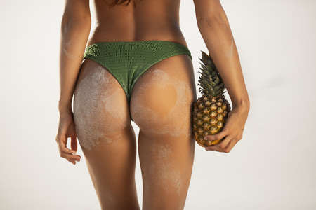 Female tanned buttocks in sand, sexy back. Sporty back of a beautiful woman in green bikini with a pineapple in her hands on the beach tropical background with copyspace. Foto de archivo - 136294322