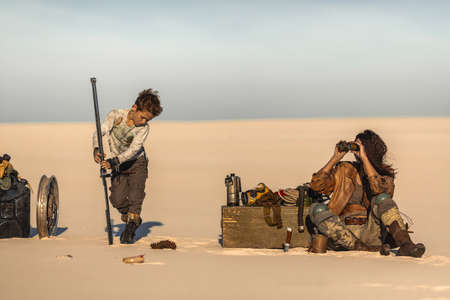 Post apocalyptic woman and boy resting in the camp outdoors. Dead wasteland on the background. Attractive fighter girl warrior in shabby clothes and a brutal kid with sword preparing for a fight. A couple of people traveling in nuclear post-apocalypse time. Life after doomsday concept.