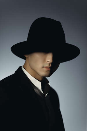 Man in suit and hat in shadow against dark background. Silhouette of a mysterious man in fedora hat. Incognito portrait