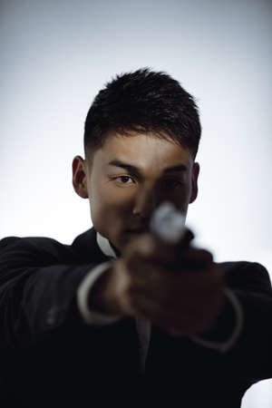 Contract Killer. Man with a gun on a light background. Portrait of elegant spy in suit with weapon