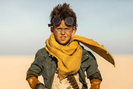 A post apocalyptic boy outdoors in desert. Nuclear post apocalypse. Life after doomsday concept. Desert and dead wasteland copy space background