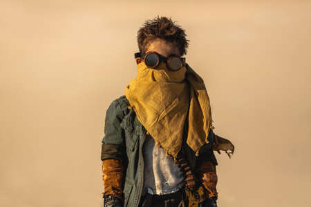 Portrait of post-apocalyptic boy outdoors in the desert. People in nuclear post-apocalypse. Life after doomsday concept. Desert and dead wasteland copy space background. A young man standing and looking to the camera