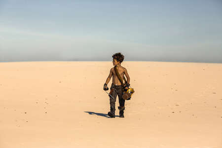 Post-apocalyptic boy outdoors in the desert. People in nuclear post-apocalypse. Life after doomsday concept. Desert and dead wasteland copy space background. A young man walking with knife, gas mask, mug looking for someone