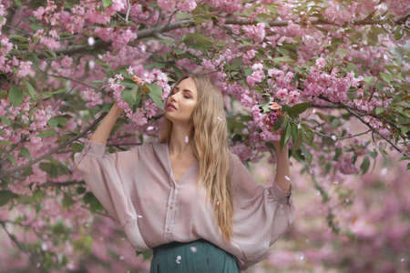 Spring girl photo. Portrait of the tender woman against the sakura flower background. Hanami celebration in sakura blooming garden. The young stylish woman standing in sakura park and enjoy the beauty of pink