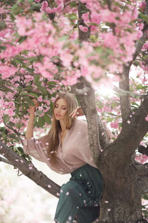 Spring girl photo. Portrait of the tender woman against the sakura flower background. Hanami celebration in sakura blooming garden. The young stylish woman standing in sakura park and enjoy the beauty of pink. Falling petals. Creative fantasy photo