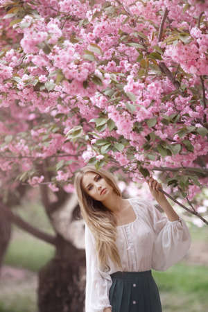 Spring girl photo. Portrait of the tender woman against the sakura flower background. Hanami celebration in sakura blooming garden. The young stylish woman standing in sakura park and enjoy the beauty of pink Фото со стока