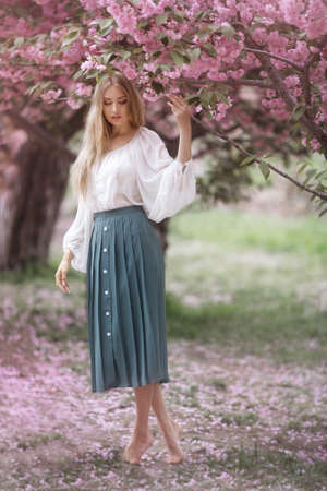 Spring girl photo. Tender woman in full length against sakura flower background. Hanami celebration in sakura blooming garden. The young stylish woman standing in sakura park and enjoy the beauty of pink Фото со стока