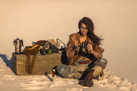 Femme héros post-apocalyptique avec des jumelles à l'extérieur. Désert et friche morte en arrière-plan. Guerrière héroïque dans des vêtements minables assis au camp. La vie après le concept apocalyptique.