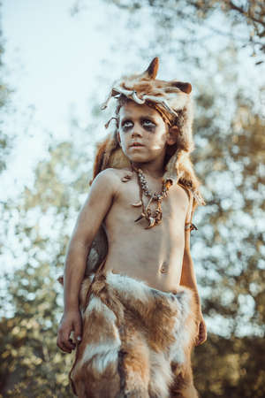 Angry caveman, manly boy. Prehistoric tribal boy outdoors on nature. Young shaggy and dirty savage, warrior and hunter. Primitive ice age man in animal skin. Reconstruction of Neanderthal and cro-magnon life