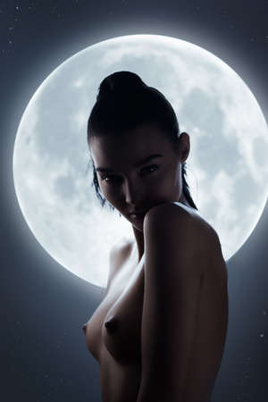 Fine art fashion studio silhouette portrait of a nude sensual woman against the night sky and a full moon. Stunning face, perfect body, slim figure, beautiful breast. Young adult mixed race Asian Caucasian model seductive look. Art of erotica