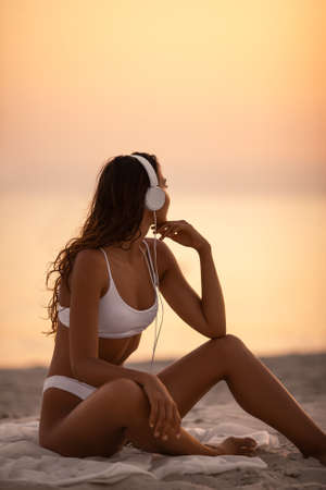 Young beautiful woman in white bikini listening to the music on the tropical beach outdoors. Tanned Mixed race Caucasian Asian slim girl sitting with headphones dressed in swimsuit relaxing at sunset, enjoying her vacations at sea. Side view. Copy space sea and sky background