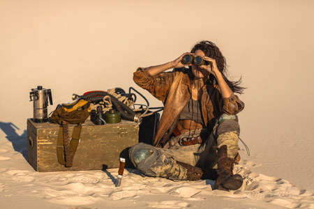 Post apocalyptic hero woman with binoculars outdoors. Desert and dead wasteland on the background. Heroic girl warrior in shabby clothes sitting at the camp. Life after doomsday concept.