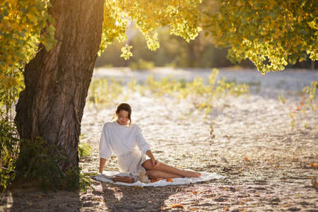 Romantic brunette woman sitting in the park at fall on a sunny day smiling and looking down. Picnic of happy beautiful woman in autumn outdoor at sunset.