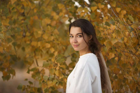 Portrait of a romantic brunette woman standing in the park at fall on a sunny day smiling and looking to the camera. The face of a happy beautiful woman in autumn outdoor at sunset.