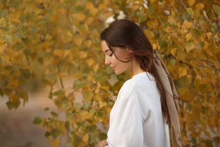 Portrait of a romantic brunette woman standing in the park at fall on a sunny day smiling and looking down. The face of a tender beautiful woman in autumn outdoor at sunset.