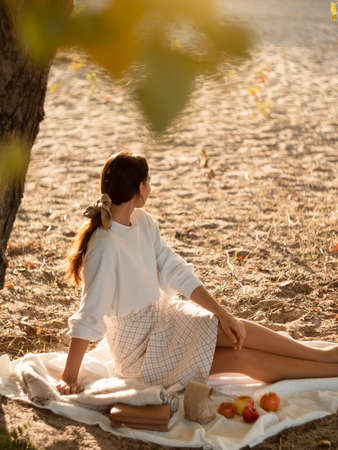 Romantic brunette woman sitting in the park at fall on a sunny day looking away. Picnic of beautiful woman in autumn outdoor at sunset. Stock fotó