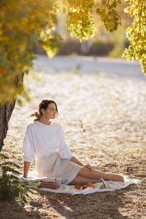 Romantic brunette woman sitting in the park at fall on a sunny day smiling and looking away. Picnic of happy beautiful woman in autumn outdoor at sunset. Stock fotó