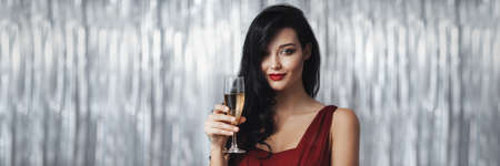 Stunning celebrating woman in the red dress. Beautiful brunette girl portrait with perfect makeup and hairstyle against holiday glowing bokeh background holding a glass wine. Fashionable luxury and festive young woman. Banner panorama with copy space for text 写真素材